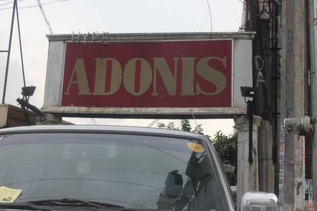 The signature gold and pink signage of Adonis Macho Dancer Bar